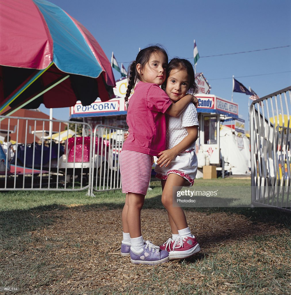 two little hispanic girls at a county fair are wearing pink and white shorts and t-shirts as they hug each other : Foto de stock
