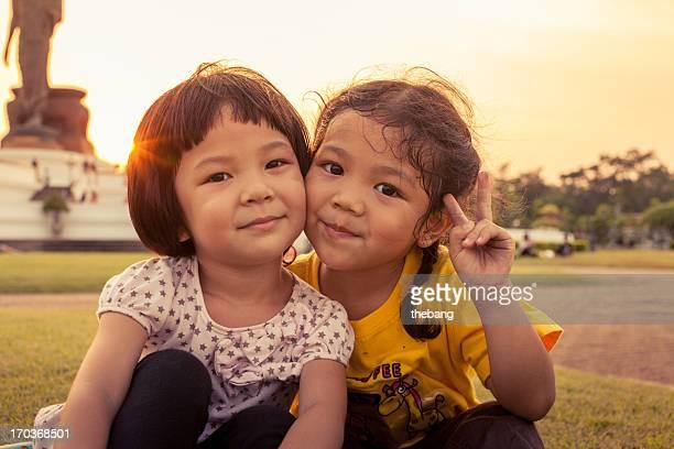 Two little kids sitting on grass