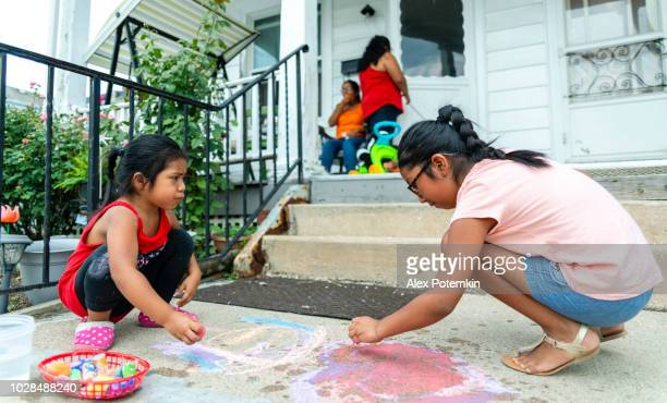 Two little Latino Mexican-American girls, sisters, drawing with chalk at the porch of his house in Pennsylvania