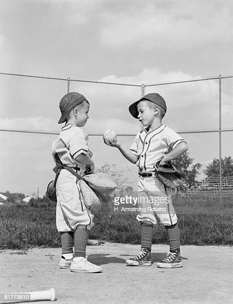 Two Little Leaguers in uniform, having discussion over ball.