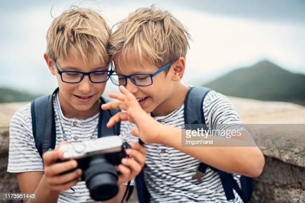 dos pequeños fotógrafos disfrutando de una nueva cámara. - gafas fotografías e imágenes de stock