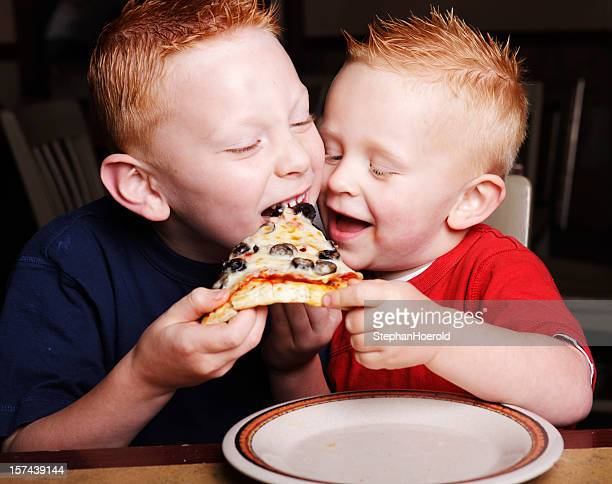Two little redheaded brothers fighting over a slice of pizza
