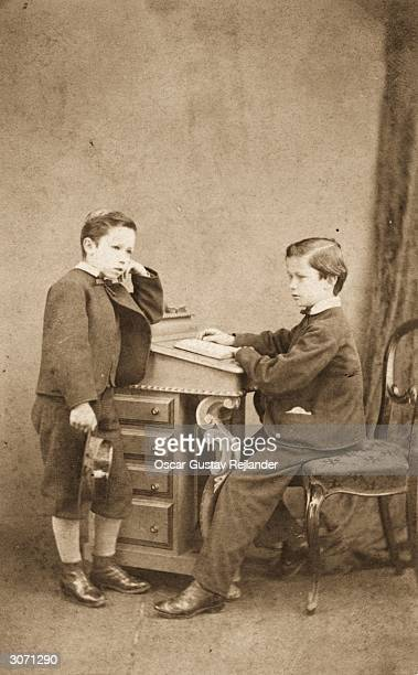 Two little schoolboys at a writing desk