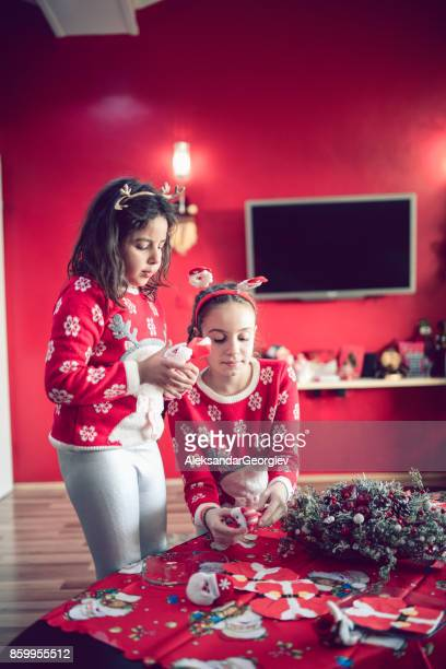 Two Little Sisters Arranging their Handmade Christmas Card for Santa