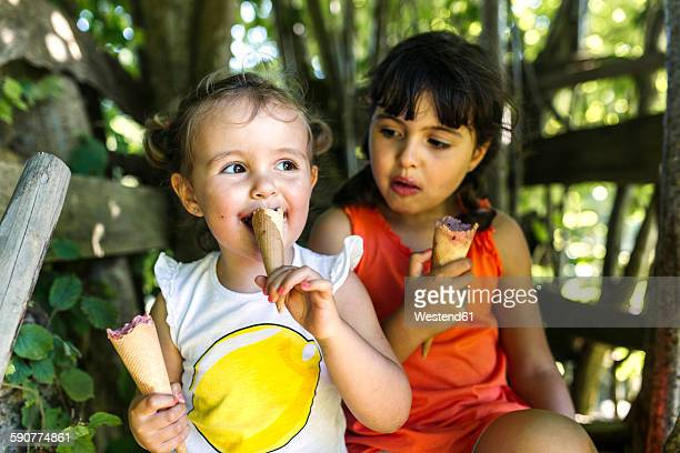 Two little sisters eating ice cream