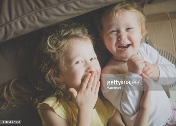 two little sisters having fun together - desaturated stock pictures, royalty-free photos & images