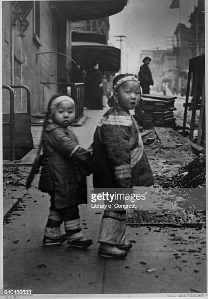 Two little sisters hold hands as they walk down the street in Chinatown San Francisco ca 1890s | Location Chinatown San Francisco California USA