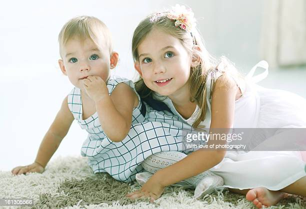 Two little sisters in beautiful dresses