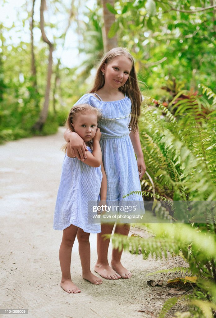 Two Little Sisters In Matching Outfits Walking Together Big Sister And Little Sister Siblings Bonde Sisters On Vacation High Res Stock Photo Getty Images