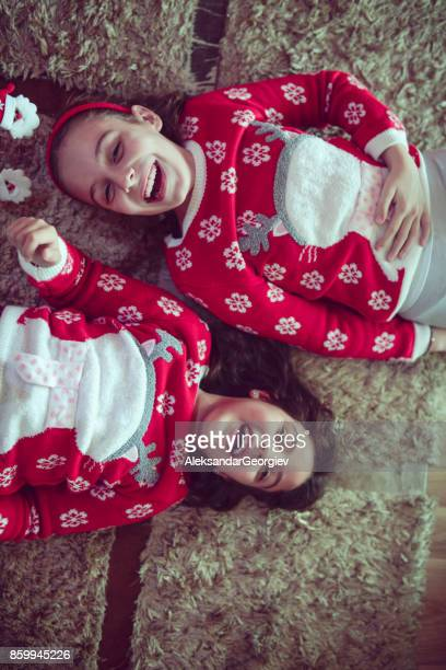 Two Little Sisters Lying on the Floor and Smiling at Christmas Night