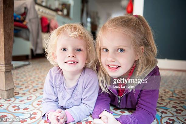 Two little sisters lying on the kitchen floor