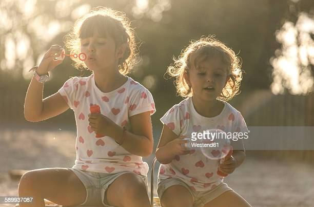 Two little sisters making soap bubbles in the park at twilight