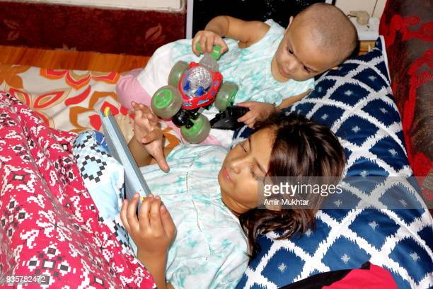 two little sisters playing with toys and tab - punjabi girls images stock photos and pictures