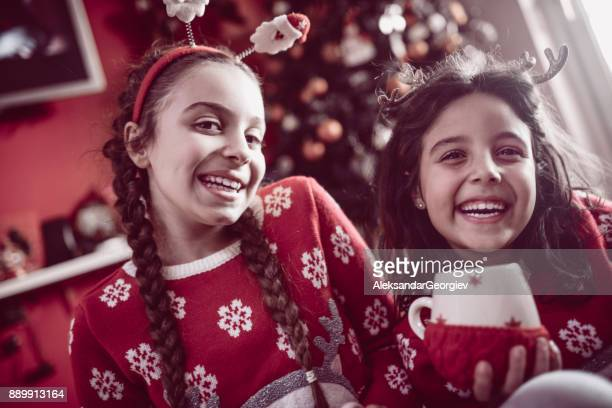 two little sisters sitting under christmas tree and drinking hot beverage - eggnog stock photos and pictures