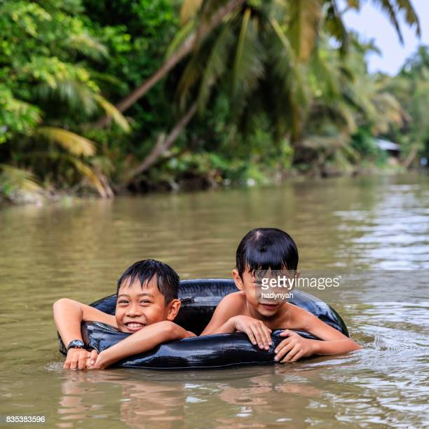 Two little Vietnamese boys bathing in Mekong River Delta, Vietnam