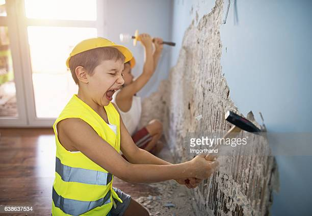 two little workers tearing out plaster in their room - vernieling stockfoto's en -beelden