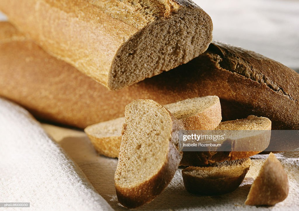 Two loaves of whole wheat bread, one whole, one cut, with slices of bread in a pile, close-up : Stockfoto