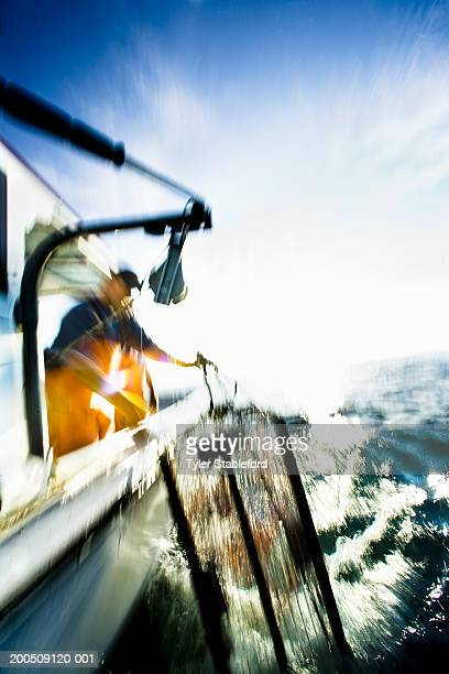 Two lobster fishermen hauling in basket (blurred motion)