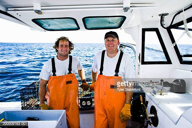 Two lobster fishermen standing on boat at sea, smiling, portrait
