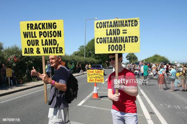 Two local Anti Frack Protesters hold placards on a main road to highlight the claims that Fracking causes contamination of water air land and the...