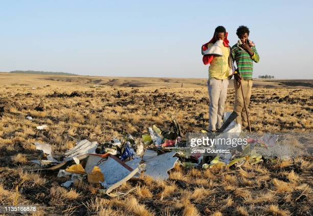 Two local boys examine a pile of twisted metal gathered by workers during the continuing recovery efforts at the crash site of Ethiopian Airlines...