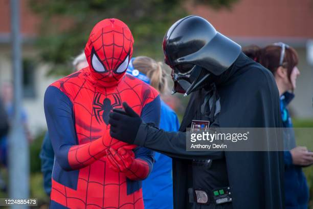 Two local charity workers dressed as superheroes look at a mobile phone as the Oldham Scottish and Manchester Community pipe bands perform during the...