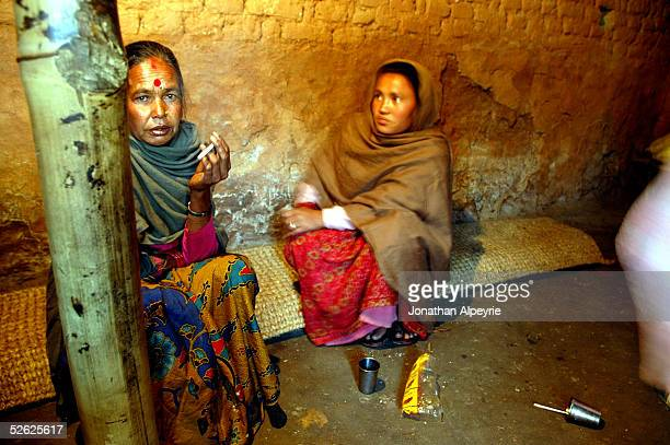 Two local Dalit mothers socialize inside the only store of the village March 2 2005 in the Kathmandu Valley village of Mulpan Nepal It is very common...