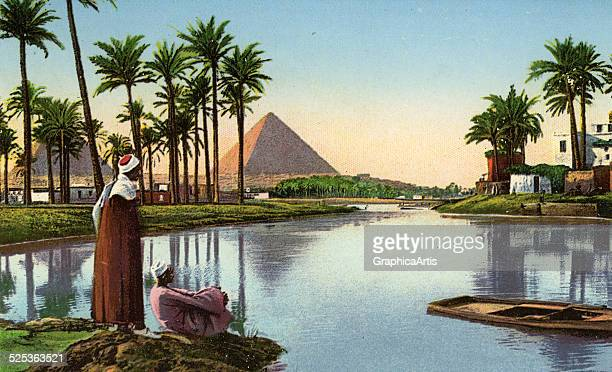 Two local Egyptian men sitting by the Nile River looking at the pyramid of Cheops in Gizeh Egypt tinted photograph circa 1900