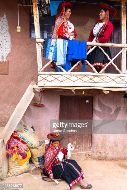 two local female weavers in colourful traditional local dress chat laughingly on the balcony of their home, while a senior woman spins wool seated below, chumbe community, lamay, sacred valley, peru (3 model releases and property release) - indigenous culture stock pictures, royalty-free photos & images