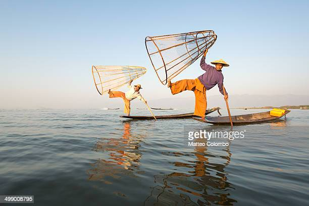 two local fishermen fishing on inle lake, myanmar - inle lake stock pictures, royalty-free photos & images
