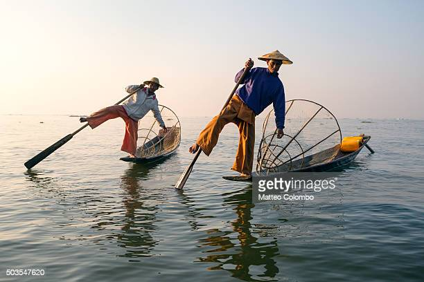 two local intha fishermen fishing on inle lake, at sunrise - myanmar culture stock pictures, royalty-free photos & images