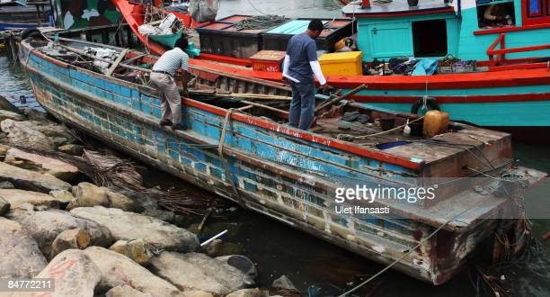 Two local men people inspect the boat used by immigrant Muslim rohingya on February 13 2009 in Aceh province on Sumatra island Indonesia...