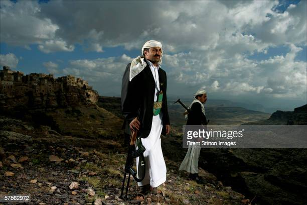 Two local men stand on the hillside outside their ancient fortresslike city on top of a mountain November 21 2005 in ShebamKawbaban Yemen Yemen has...