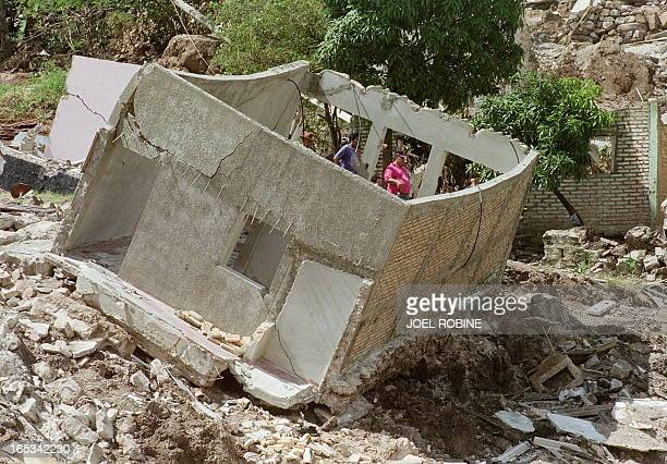 Two local residents pass nearby a destroyed house in Tegucigalpa 13 November after Hurricane Mitch hit the country. Officials report that more than...
