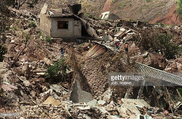 Two local residents pass nearby a destroyed house in Tegucigalpa 13 November 1998 after Hurricane Mitch hit the country Officials report that more...