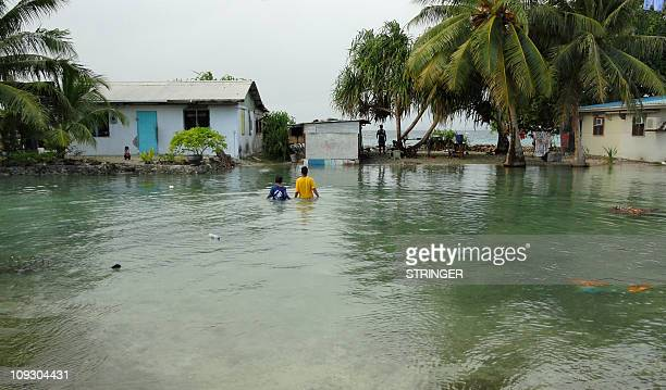 Two local residents wade through flooding caused by high ocean tides in lowlying parts of Majuro Atoll the capital of the Marshall Islands on...