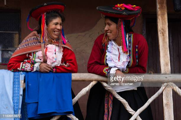 two local woman weavers in colourful traditional local dress look down laughingly from the balcony of their home, chumbe community, lamay, sacred valley, peru (2 model releases and property release) - indigenous culture stock pictures, royalty-free photos & images