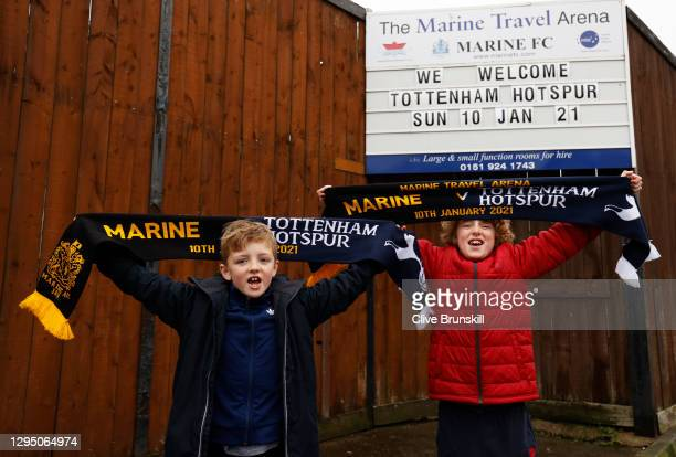 Two local young Marine FC fans pose for a photograph with their match day scarves in front of the clubs board displaying their next home game the FA...