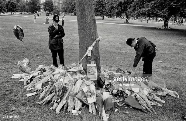 Two London policemen read the messages left with bouquets of flowers in Kensington Gardens near Kensington Palace home of Diana Princess of Wales...