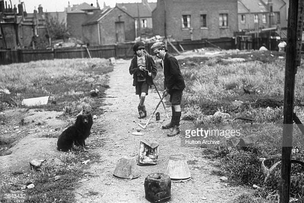 Two London slum boys playing golf on a home made course, consisting of old buckets.