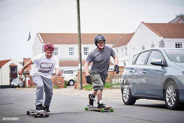 two long boarders enjoying a ride - skating stock pictures, royalty-free photos & images