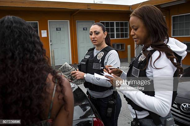 Two Los Angeles police officers both from the Human Trafficking Task Force question an unidentified female suspect in a motel parking lot on South...