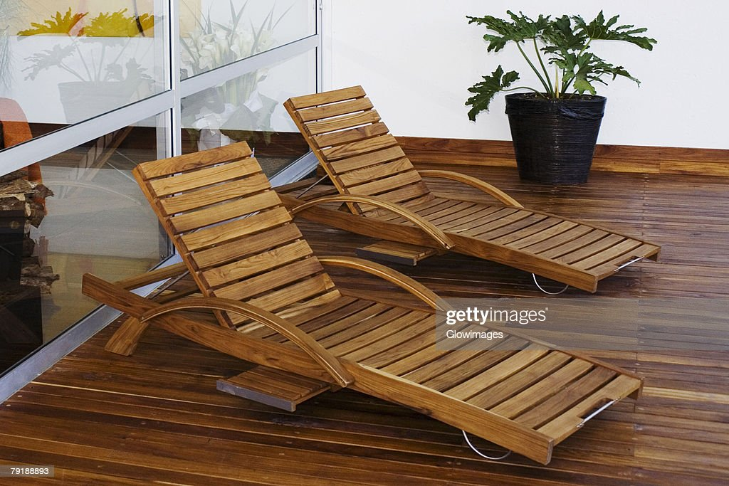 Two lounge chairs in a patio of a house : Stock Photo