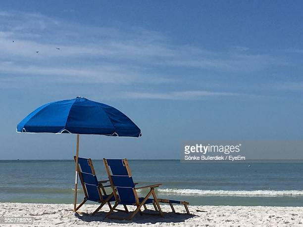 Two Lounge Chairs Under Beach Umbrella