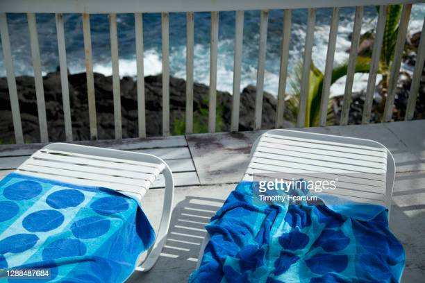 two lounge chairs with colorful beach towels on a balcony/deck; lava rock and ocean below - timothy hearsum stock pictures, royalty-free photos & images