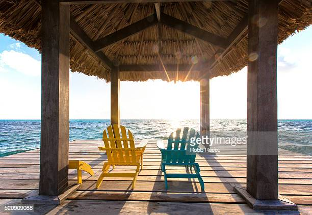 two lounge deck chairs on a dock near a belize resort at sunrise - robb reece stockfoto's en -beelden