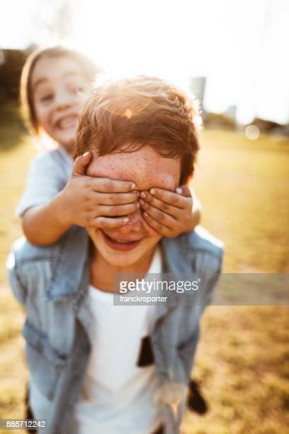 two lovely kids piggyback at the park