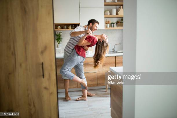 two lovers dancing in the kitchen. - coppia di giovani foto e immagini stock