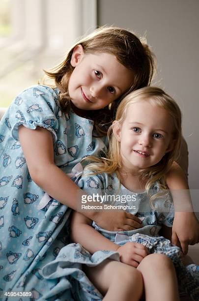 Two loving sisters sitting in matching nightgowns