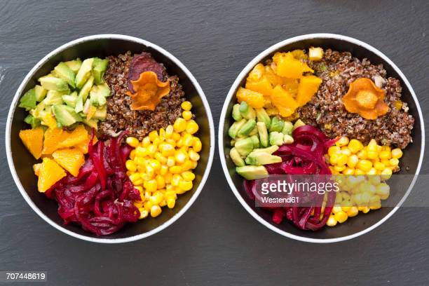 Two lunch bowls of red quinoa, beetroot, corn, avocado, orange and vegetable chips